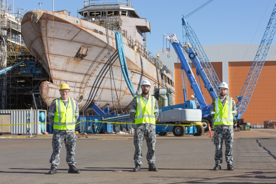 Chief Petty Officer Marine Technician Mark Verhoeven (left), Leading Seaman Electronics Technician Jimmy Savage (centre) and Lieutenant Commander Jonathon Robarts (right) with NUSHIP Arafura at the Osborne Naval Shipyard.