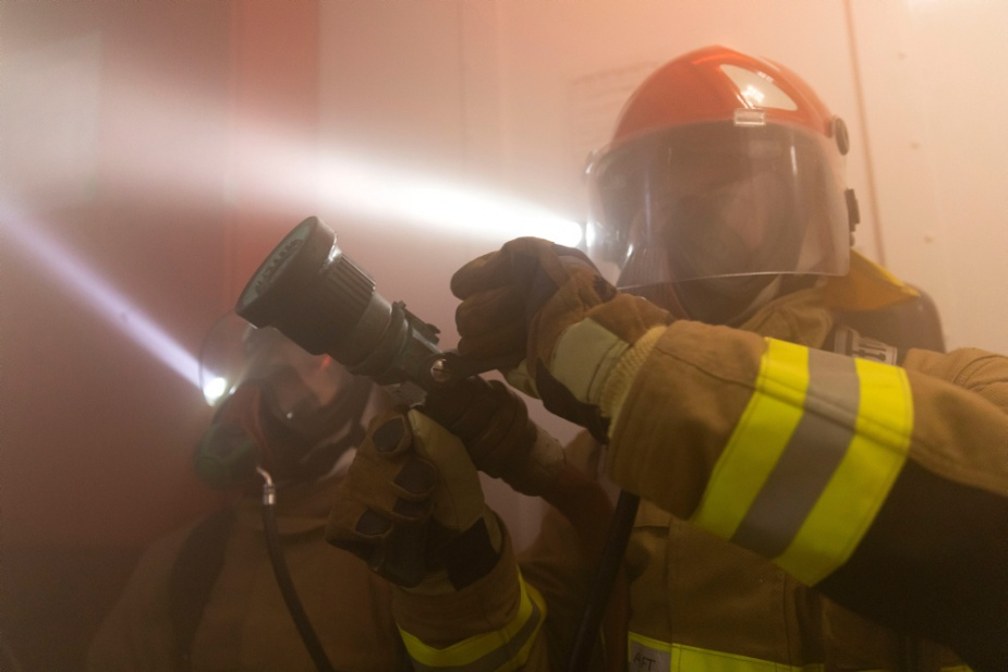 Lieutenant Aviation Warfare Officer Lachlan Murray, left, and Able Seaman Electronics Technician Ethan Jones fight a simulated fire during a Damage Control Exercise onboard HMAS Arunta. Photographer: LSIS Jarrod Mulvihill.