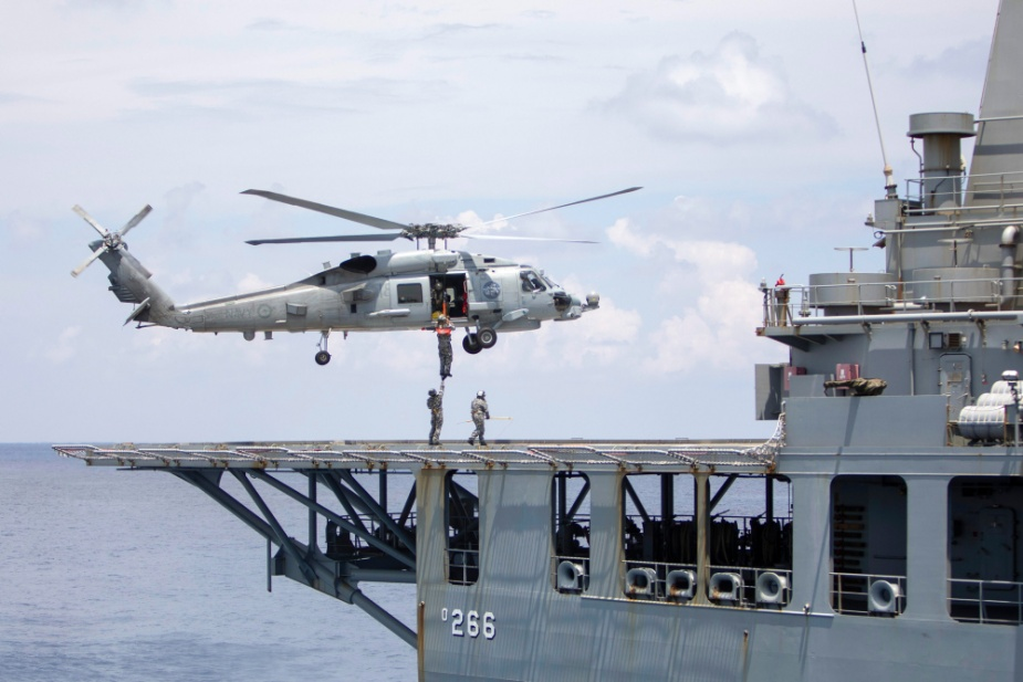 A MH-60R helicopter winches personnel onto the flight deck of HMAS Sirius during a replenishment-at-sea in the Karimata Strait.