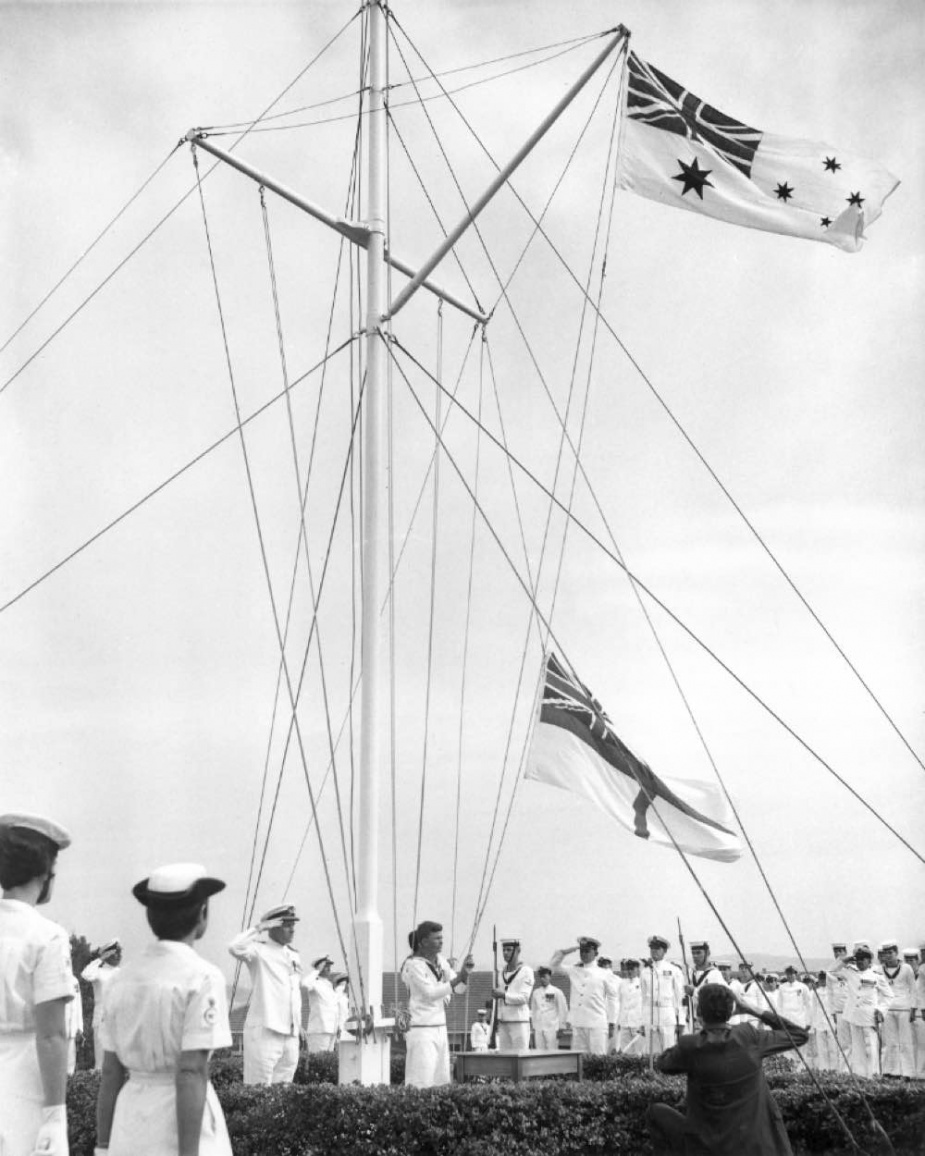 The Royal Navy White Ensign is lowered for the last time in a ceremony at HMAS Watson, 1 March 1967.