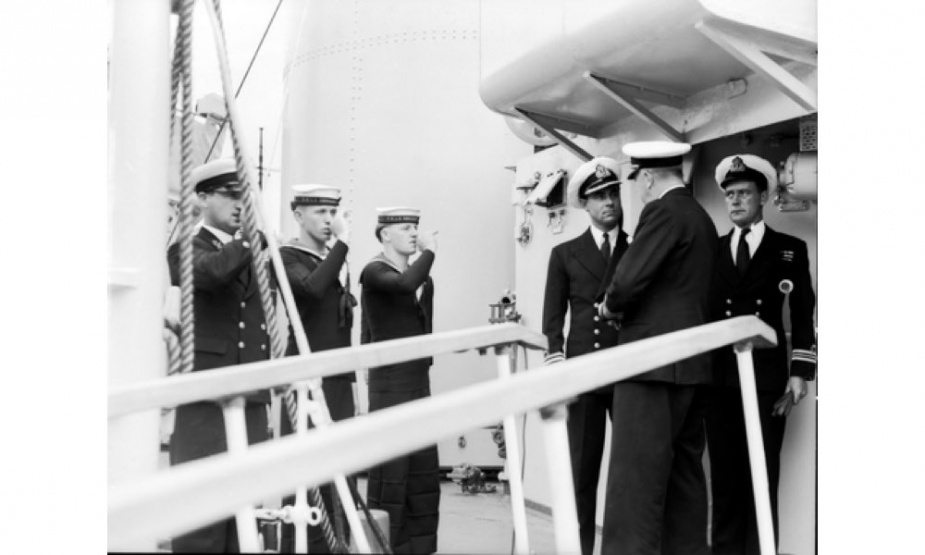 Rear Admiral JAS Eccles, Flag Officer commanding the Australian fleet, is piped aboard HMAS Shoalhaven at Kure Harbour. Meeting him at the head of the gangway are Commander I H McDonald (left) and Lieutenant Commander A Sangster (right) (AWM HOBJ0718).