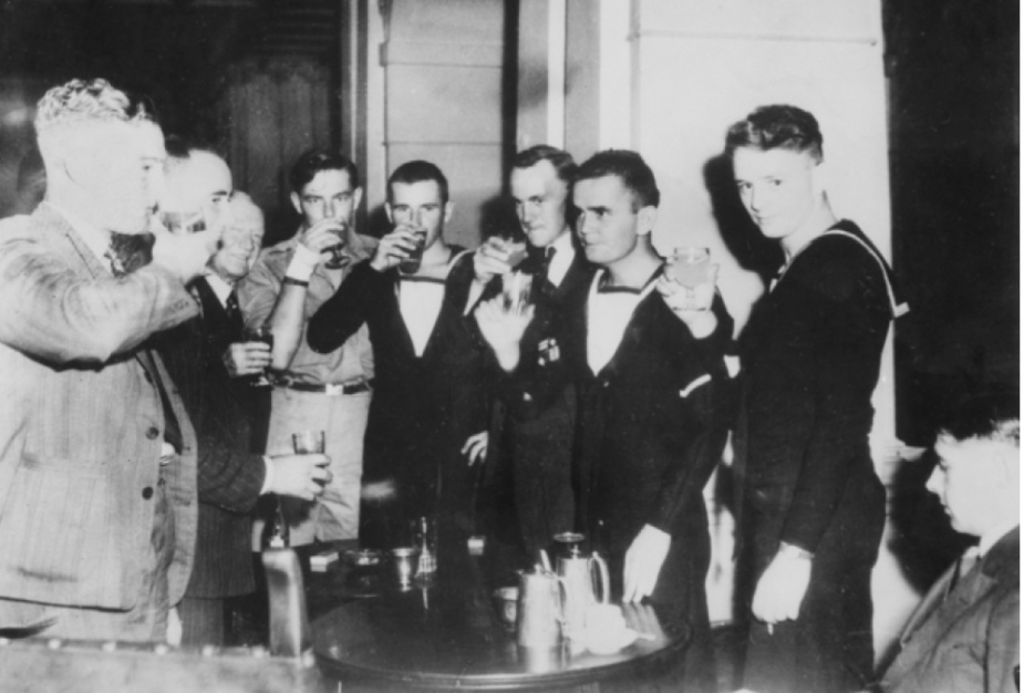"""Eight of the survivors enjoying a drink at the Menzies Hotel, Melbourne.The ship's whaler with twenty nine survivors, commanded by Lieutenant LG Palmer was also rescued by HMAS Kalgoorlie on 9 December 1942. During the epic voyage in the ship's whaler Wireman Bill Lamshed celebrated his 22nd birthday on 7 December 1942. Palmer offered to """"shout the Melbourne lads dinner at the Menzies"""" if they survived the voyage. Left to right: Assistant Cook GC Sanderson; Ordinary Seaman JP Parker; the hotel manager; Ordinary Seaman RC Wilson; Ordinary Seaman VR Leonard; Wireman WN Lamshed; Signalman GR Devlin and Ordinary Seaman RM Caro. (Courtesy of Ray Raymond)"""