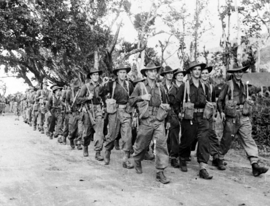 Members of the 6th Australian Division marching to the beachhead of But Beach, New Guinea to board HMAS Colac and her sister ship HMAS Dubbo in preparation for the amphibious assault on the Wewak Peninsula, circa May 1945. (AWM 018495)