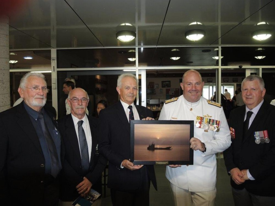 Members of HMAS Labuan's commissioning crew presenting the Fleet Commander with a framed sunset photo of HMAS Brunei commemorating the sun setting on the LCH era in the RAN, 19 November 2014. L to R: Larry Ogden, Bob Davis, Wayne Ferguson, Rear Admiral S Mayer, CSC*, RAN and Bruce McCoist (Wayne Ferguson collection).