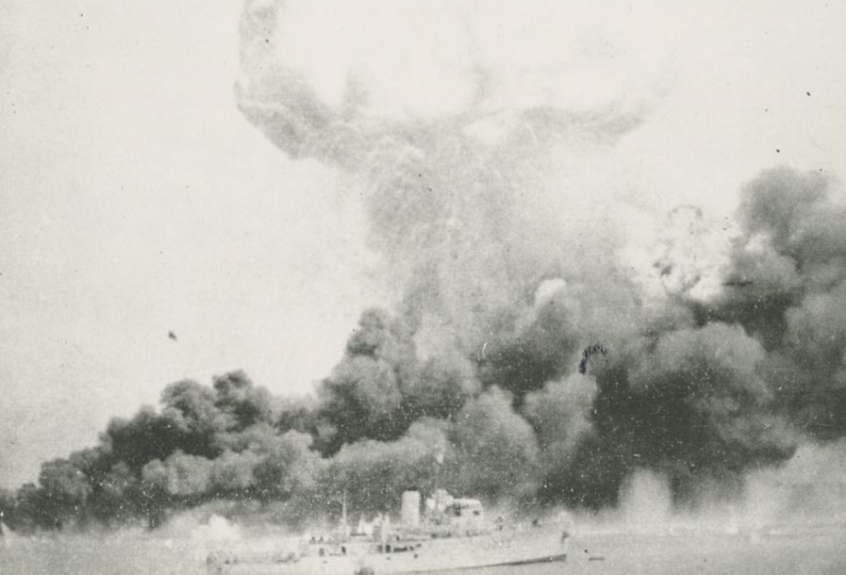 Darwin. Oil Tanks on Fire. HMAS Deloraine in foreground. The mushroom cloud is from the explosion of the ammunition ship Neptuna. Telegraphist R. Belbin, RAN.