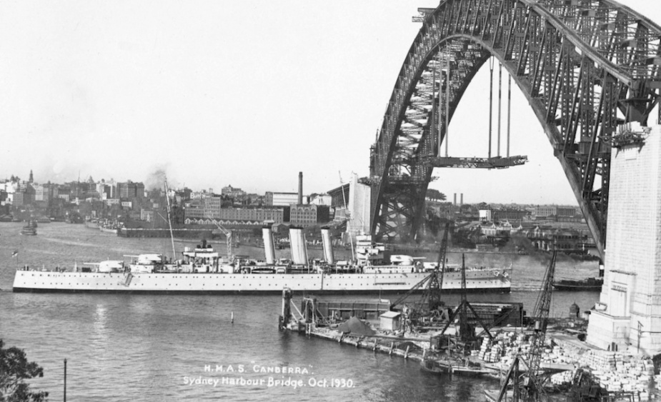 HMAS Canberra passing under the still being constructed Sydney Harbour Bridge, October 1930