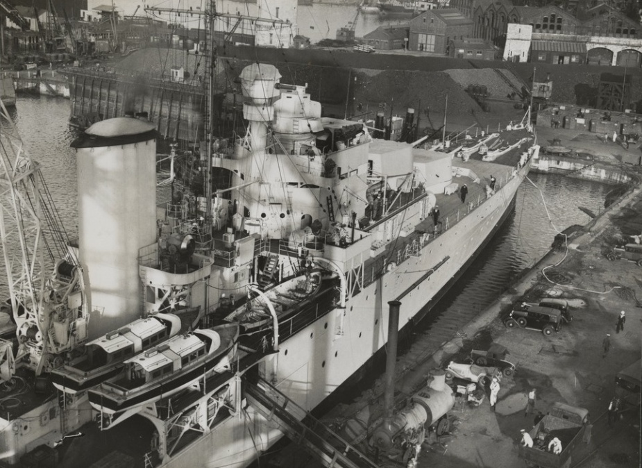 Sydney's seaplane crane visible mounted immediately behind her forward funnel. The crane's jib is in the raised position
