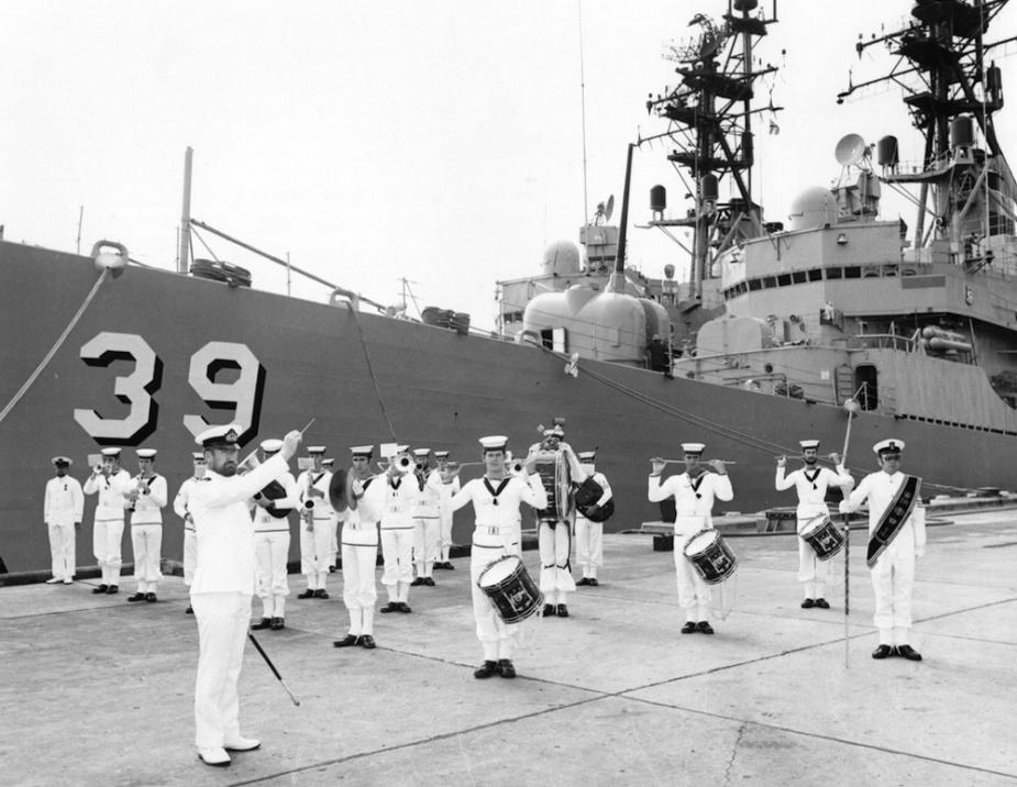 HMAS Hobart (II) forms the backdrop to the RAN fleet band alongside Garden Island, Sydney, circa 1972.