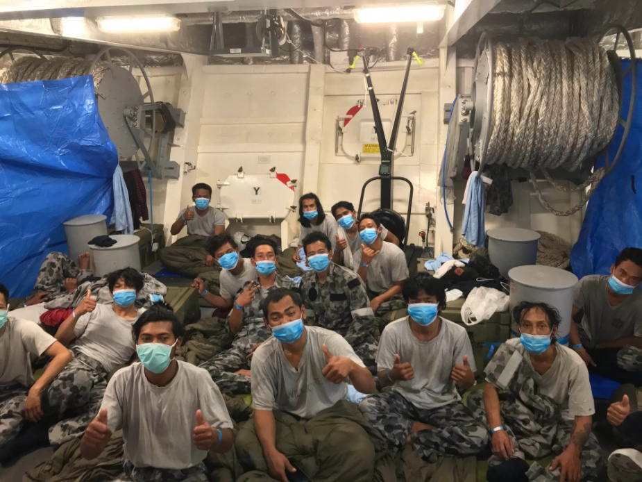 Indonesian fishermen rescued in the Indian Ocean are accommodated on HMAS Anzac's quarterdeck.