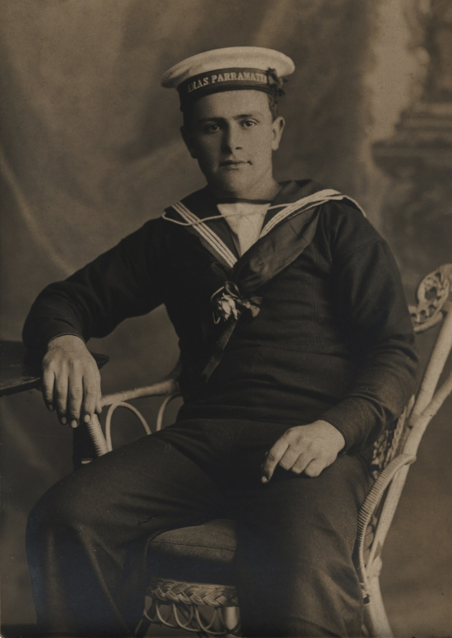 A seaman of HMAS Parramatta poses proudly in his uniform with cap ribbon clearly visible.