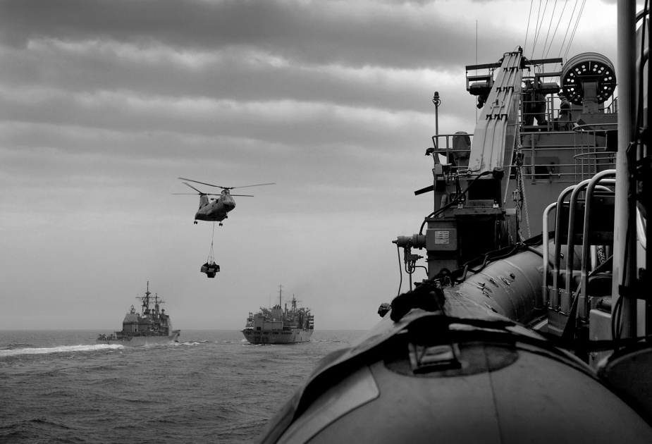 A Sea Knight transfers stores to HMAS Manoora during Operation SLIPPER