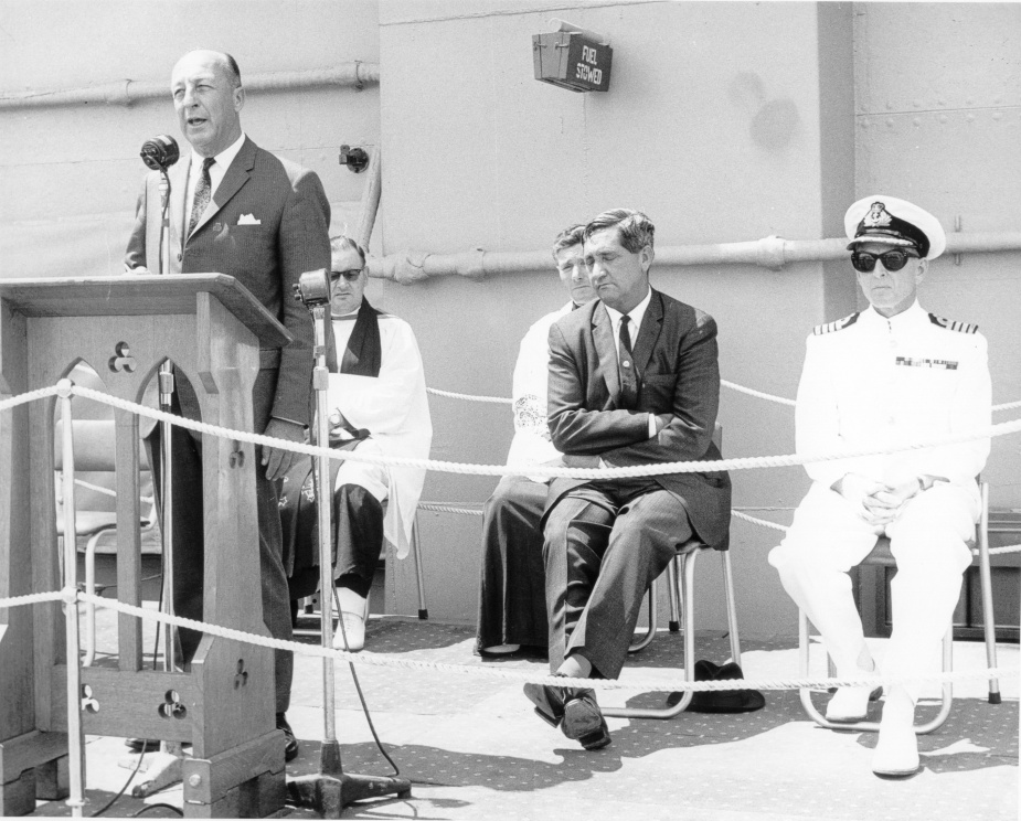 The Minister for Defence, the Hon Allen Fairhall, MP, addressing the audience at Melbourne's re-dedication ceremony on 14 February 1969. Behind him from left to right are Chaplain Alan Batt, Chaplain Louis Breslan, the Minister for the Navy, the Hon Charles 'Bert' Kelly, MP, and Melbourne's commanding officer, Captain John Stevenson, RAN.