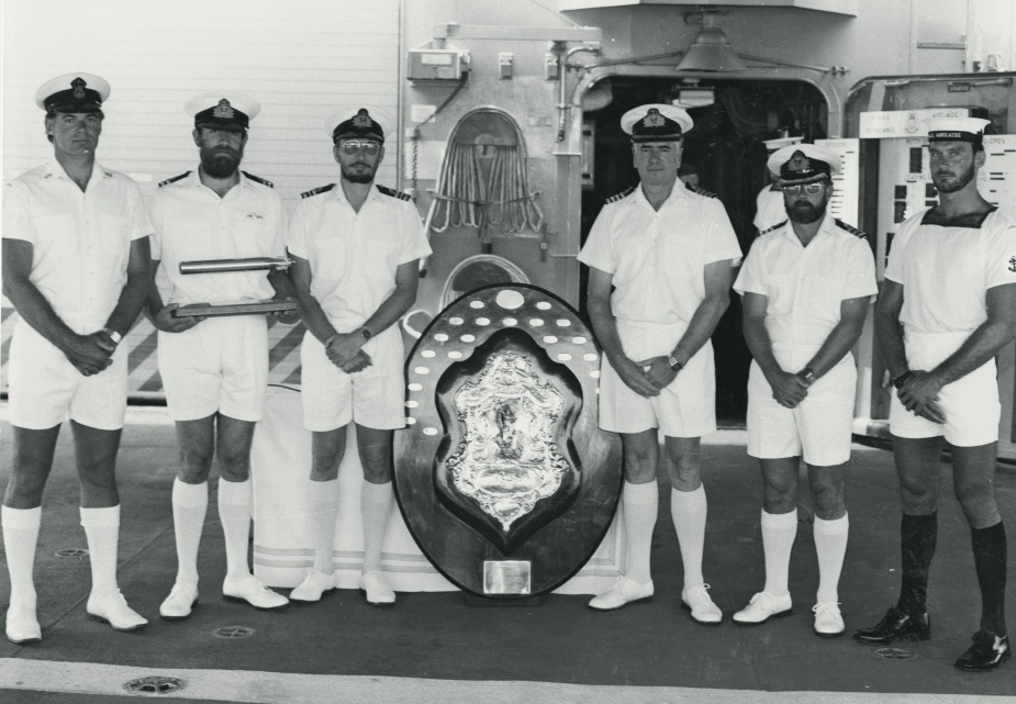 Commanding Officer HMAS Adelaide (II) Captain A.M. Carwardine and his charges proudly present the Otranto Shield earnt by the ship in 1984.