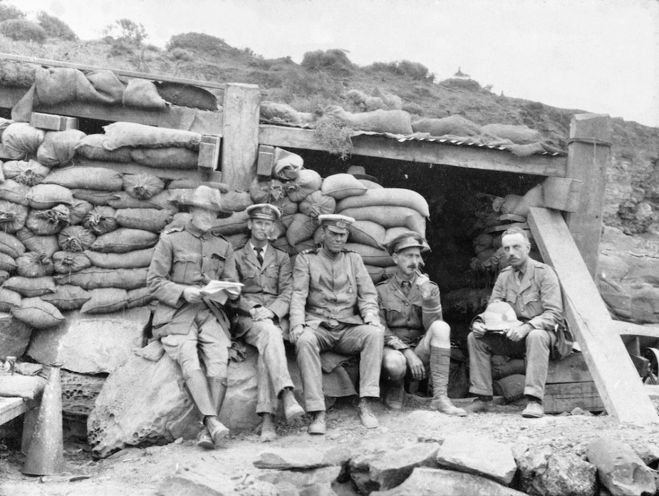 Bracegirdle seated outside his 'hole in the ground' L-R: Staff Surgeon Morris, RANR, Lieutenant Commander LS Bracegirdle, RAN, Lieutenant T Bond, RANR, Captain McRitchie, Major Jellicoe. (AWM P01326.002)