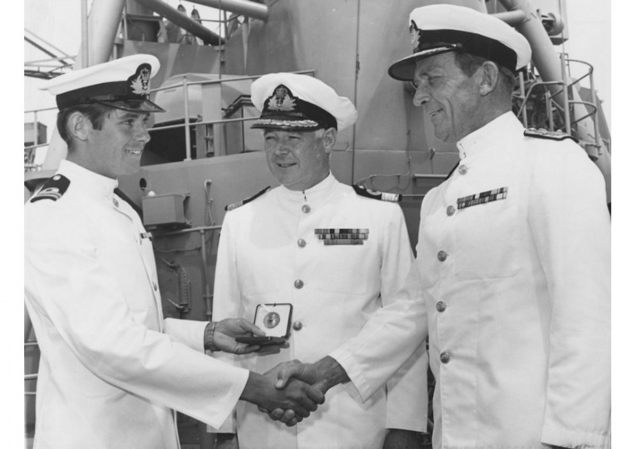 Rear Admiral GJB Crabb (right) the then Flag Officer Commanding East Australia Area, congratulates Lieutenant David Ramsay of the destroyer HMAS Brisbane on receiving the Queen's gold medal in Sydney on the 24th of October 1971. Lieutenant Ramsay was the son of the then Naval Officer Commanding West Australia, Commodore JM Ramsay (centre). He entered the Navy in January, 1963. During his time in the United Kingdom he obtained best overall marks in his final year of initial training for seaman and supply off
