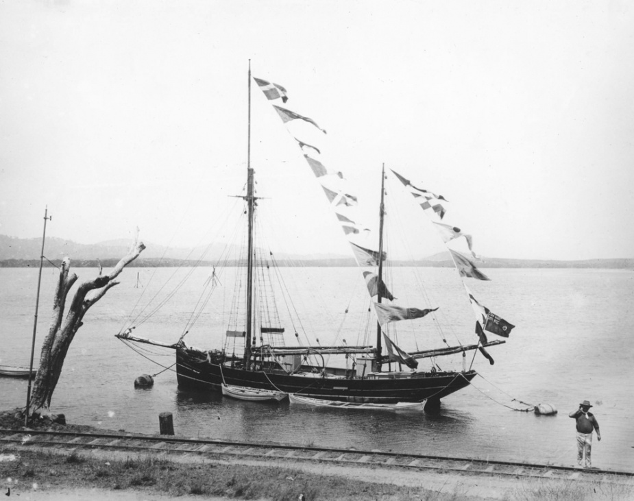 The colonial ship Spitfire at Cooktown in the late 19th century. Note the colonial flag flown from her ensign staff.