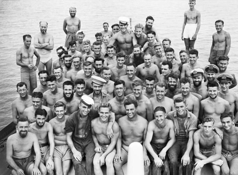 Members of the crew of Mildura grouped forward of the 4-inch gun off Tarakan Island, circa 1945. (AWM 110293)