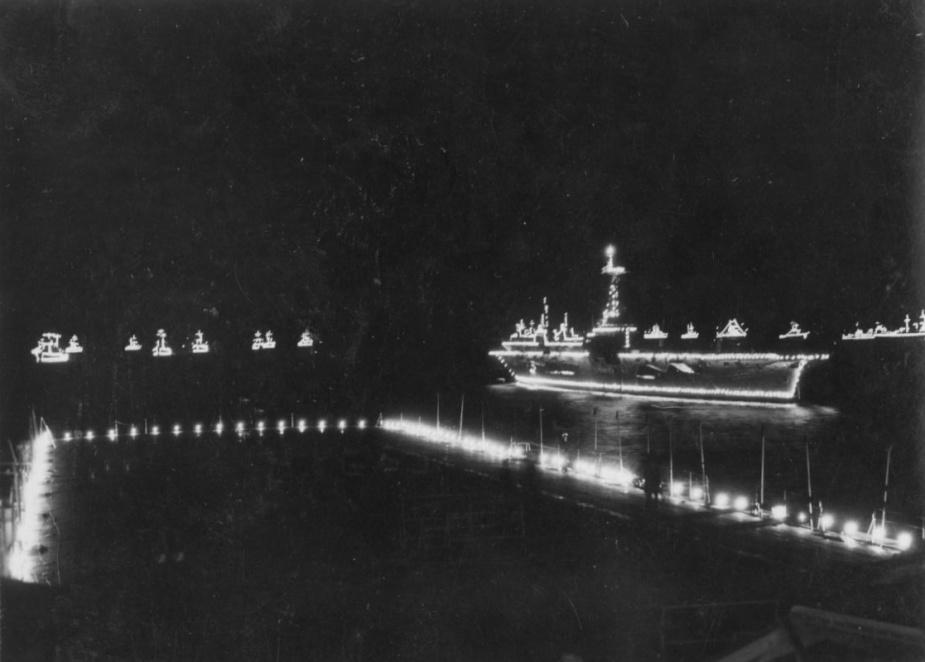 The coronation fleet illuminated with festoon lighting as seen from Sydney's island.