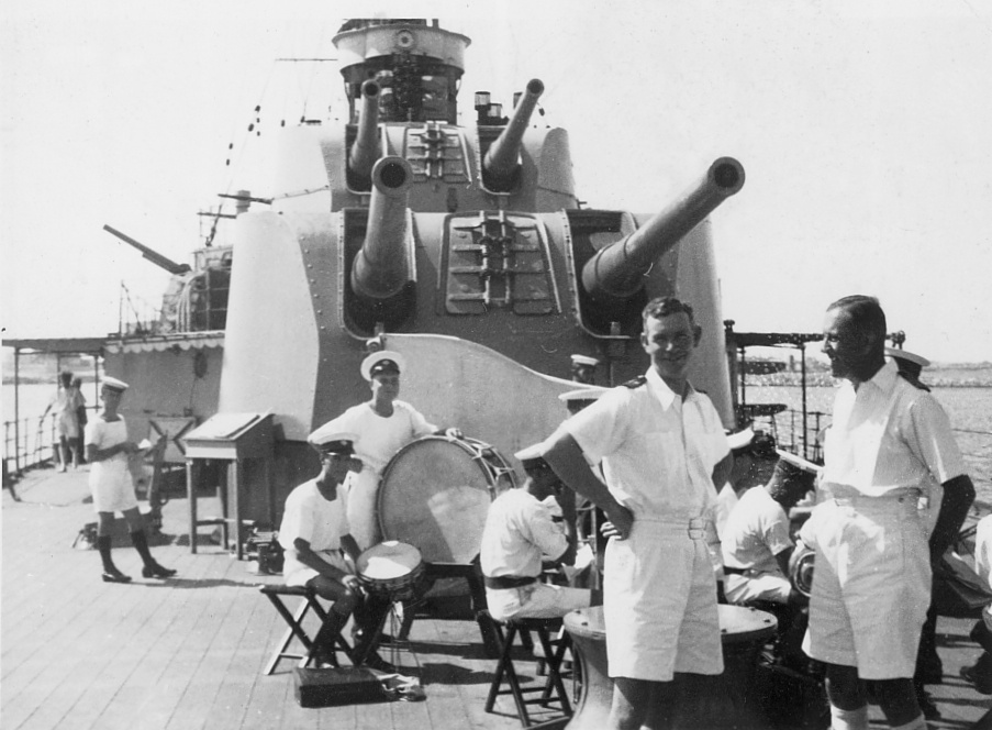 A view looking forward of Sydney's two aft 6-inch guns. In the foreground stands Lieutenant Commander R.D. Handcock (left) one of Sydney's engineering officers. Behind him members of Sydney's band can be seen practising.