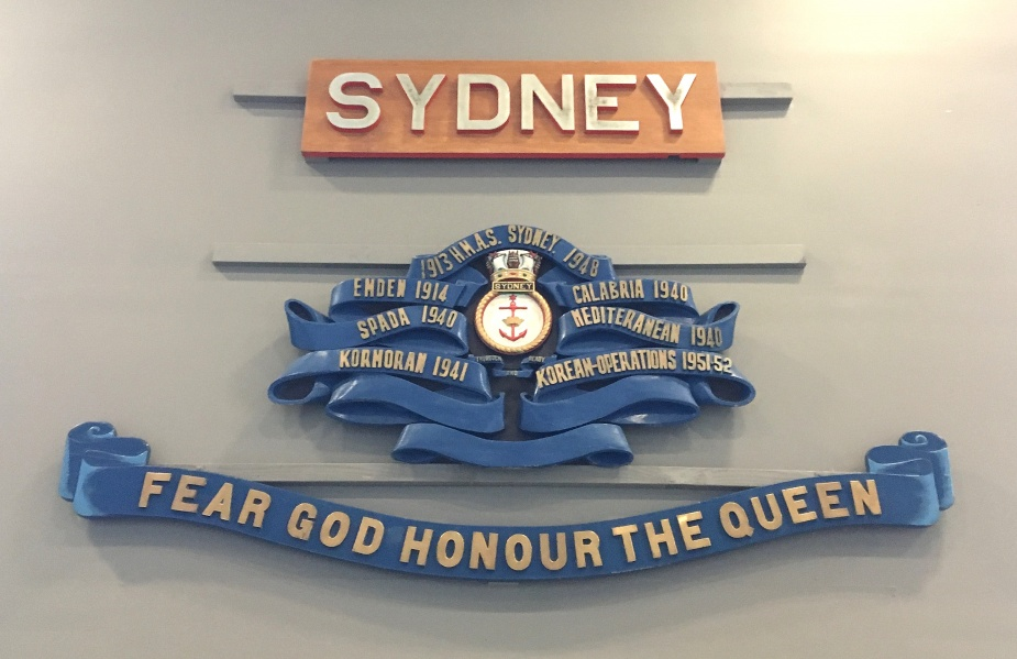 The Battle Honour Board carried by HMAS Sydney (III). Following the adoption of the 1954 policy in the RAN, efforts were made to standardise the appearance of battle honour boards which were henceforth made of teak.