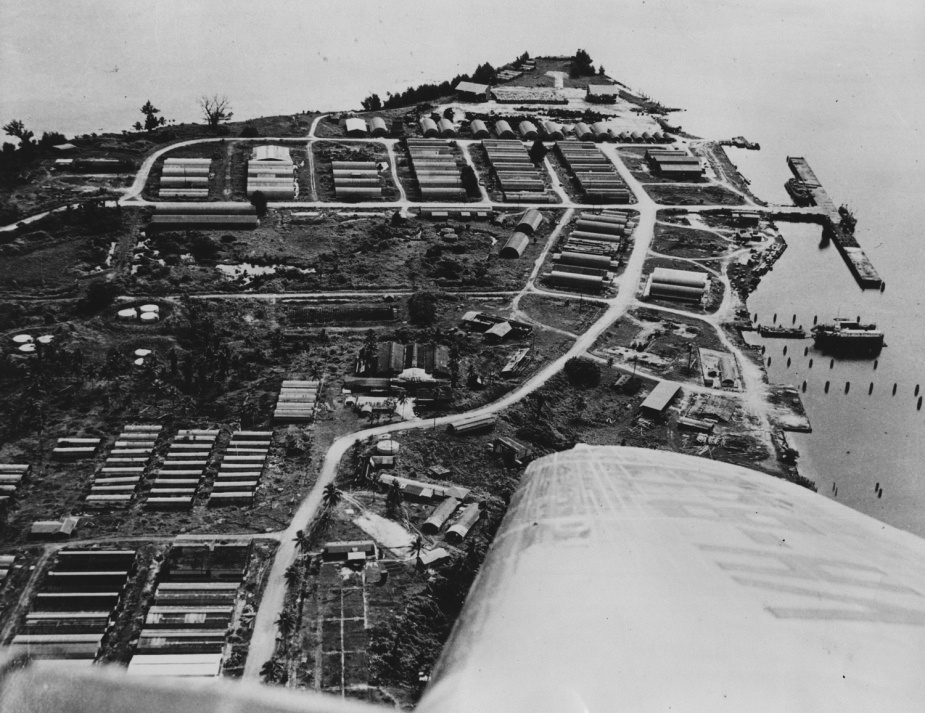 An overflight of Tarangau showing the wharf area and rows of WWII-era Quonset huts that were used variously as workshops, storage facilities and for accommodation.