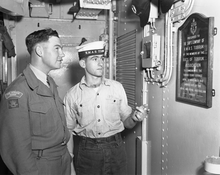 Private (Pte) Edwin Henry Cowley, 1st Battalion The Royal Australian Regiment (1RAR), of Murray Bridge, SA, is listening with interest to the history of the mess hall plaque. Able Seaman (AB) Peter Stokes, of Black Forest, Adelaide, SA, explains that all the crew are honorary members of the Rats of Tobruk Association which had adopted the ship in memory of the Tobruk ferry service in 1941