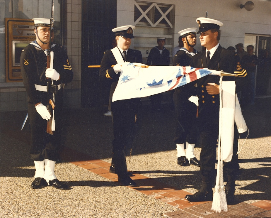 The Australian White Ensign is uncased by POQMG Tony Howard on the occasion of HMAS Tobruk's inaugural granting of Freedom of Entry into the City of Lake Macquarie on 9 August 1991. Visible in the escort party are: L-R: LSQMG Dean Faunt, SBLT MJ Kear and LSQMG Chris Bryant.