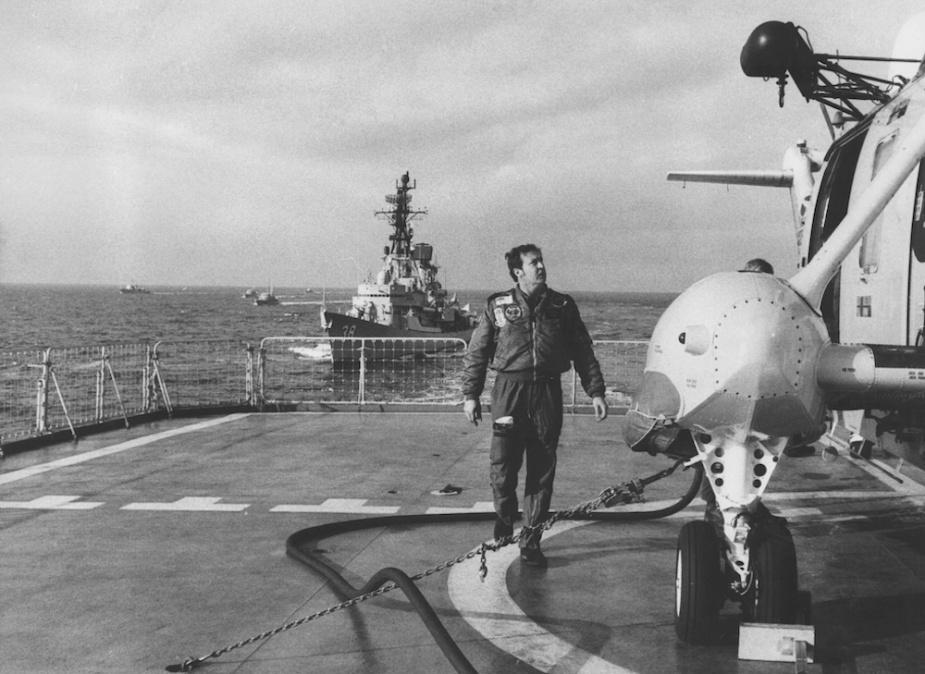 Aviation Technician Bob Ferry inspects aircraft on Tobruk's flight deck, 1984.