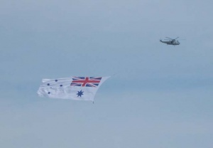 RAN Sea King flies the White Ensign at the HMAS Albatross 60th Anniversary Air Show.