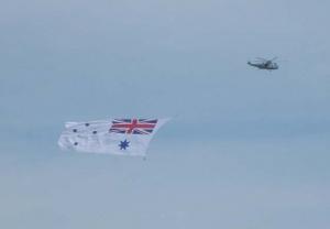 RAN Sea King flies the White Ensign at the HMAS Albatross 60th Anniversary Air Show.