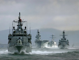 Joint Maritime Course (JMC) exercise. Pictured is a Carrier Group containing, L-R: Turkish ship TCG Oruçreis, British Aircraft Carrier HMS Illustrious, American Ship USS McFaul, British Ship HMS Westminster and Danish Ship HDMS Ravnen. Image by (then) Petty Officer Imagery Specialist Damian Pawlenko in 2005.