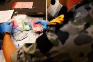 A Boarding Officer goes through an evidence bag onboard HMAS Wollongong. Photographer: SGT Rob Nyffenegger 2010.