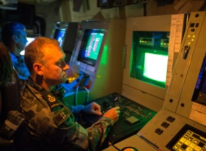 Chief Petty Officer Sean Huron pilots HMAS Huon's Unmanned Underwater Vehicle from the Operations Room during a requisition dive to find a mine shape.