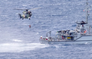 """HMAS Choules' embarked MRH-90 Taipan helicopter, call sign """"Hat Trick"""", conducts passenger transfer serials with HMAS Huon during the ship's transit to Vanuatu. Photographer: LSIS James McDougall."""