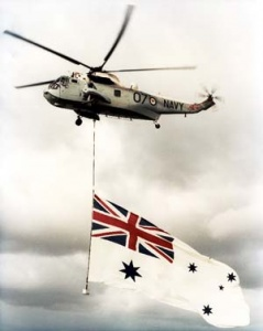 A RAN Sea King flies the White Ensign.