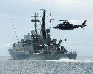 RAN Agusta Westland A109E above HMAS Larakia.