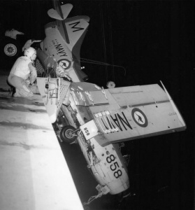 Gannet 858 precariously suspended over Melbourne's port side after the pilot had unsuccessfully attempted to 'wave off' his landing. The aircrew was rescued but efforts to recover the Gannet were unsuccessful and it was eventually released overboard.