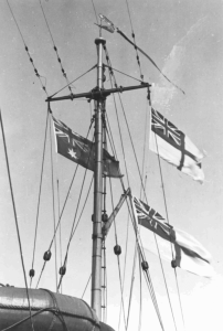 HMAS Bathurst (I)'s main mast proudly flying the Australian National Flag and multiple White Ensigns.