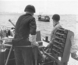 HMAS Hawk's gun crew at the ready as the ship intercepts a vessel off Borneo.