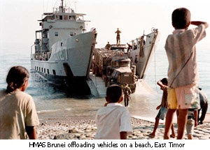 HMAS Brunei offloading vehicles on a beach, East Timor