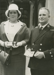 Mrs Lorraine Rogers and Chief Petty Officer Douglas Moore display the awards which were presented to them by HM the Queen on 8 July 1965. Mrs Rogers is the widow of Chief Petty Officer Johnothan Rogers who was awarded the George Cross posthumously for gallantry during the sinking of HMAS Voyager. Chief Petty Officer Moore was awarded the George Medal. (RAN Navy News, 6 August 1965)